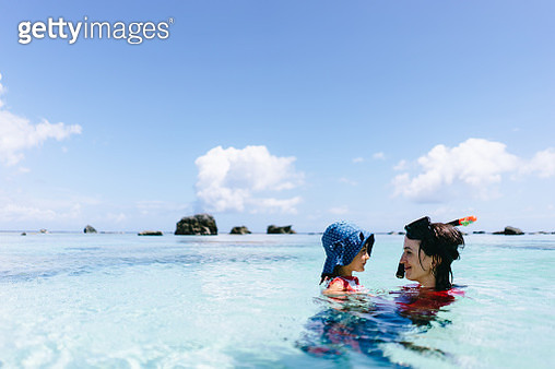 Mother and child having intimate moment in clear tropical water, Japan - gettyimageskorea
