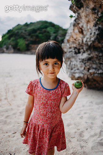 Cute toddler girl holding guava and smiling at camera on beach - gettyimageskorea