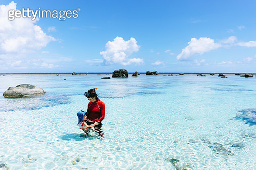 Mother and child playing in coral lagoon, Amami Islands, Japan - gettyimageskorea