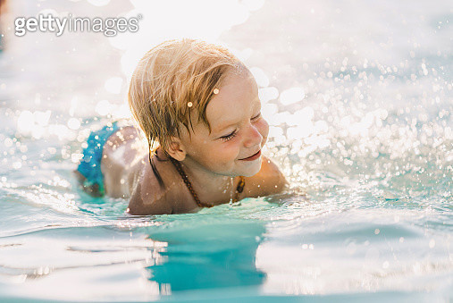 Happy little boy enjoying in swimming pool during summer day. - gettyimageskorea