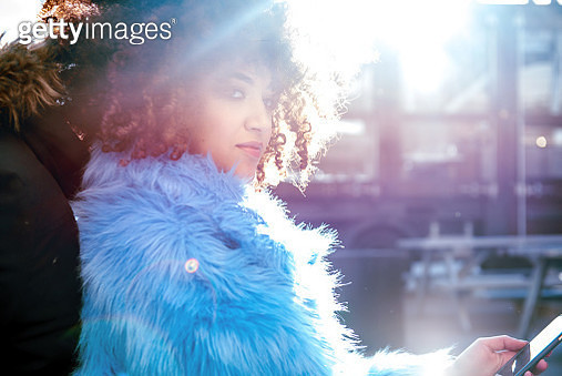 Portrait of woman with afro and fur coat looking away - gettyimageskorea