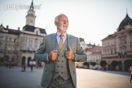 Cheerful senior businessman on a town square - gettyimageskorea
