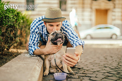 Young man in the city with his french bulldog - gettyimageskorea