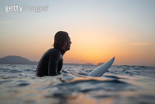 Side View Of Man Surfing In Sea Against Sky During Sunset - gettyimageskorea