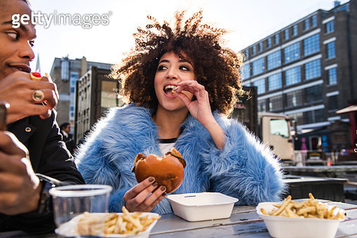 Young couple eating burger and chips outdoors - gettyimageskorea