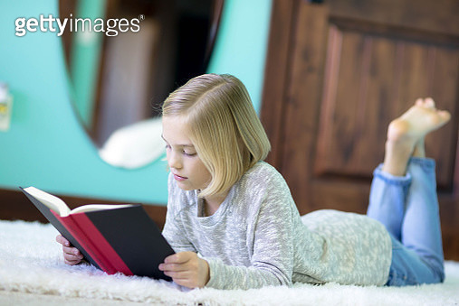 A blonde elementary age girl reads in her bedroom - gettyimageskorea