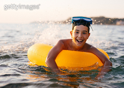 Boy having fun splashing in sea - gettyimageskorea