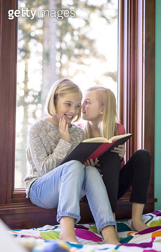 Sisters reading a book together in a window seat - gettyimageskorea