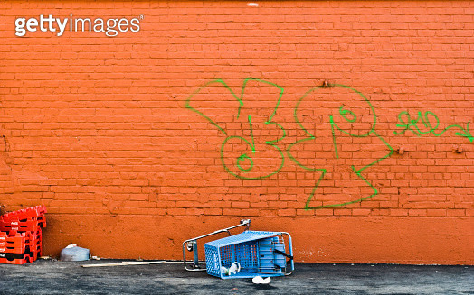 Over turned shopping cart against a graffiti strewn wall. - gettyimageskorea