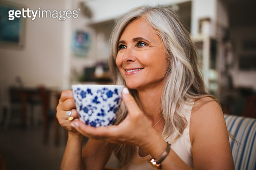 Portrait of beautiful mature woman drinking tea at coffee shop - gettyimageskorea