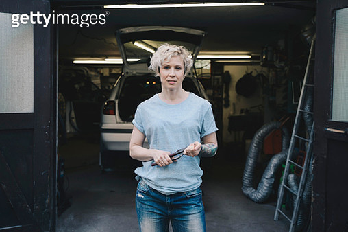 Portrait of female owner holding work tool while standing at entrance of auto repair shop - gettyimageskorea