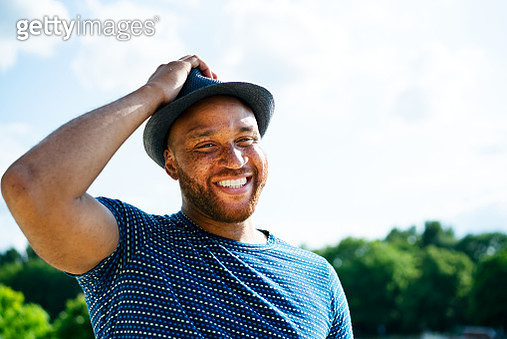 Smiling man with hand on hat - gettyimageskorea