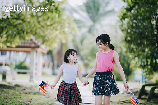 an asian chinese sisters running in the public park with malaysia national flag happily - gettyimageskorea