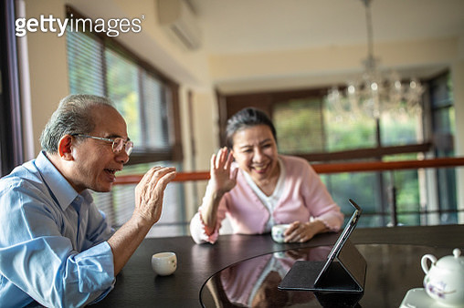 Modern, Taiwanese Senior couple using digital tablet for video call, sitting  in the dining room at home together, waving - gettyimageskorea