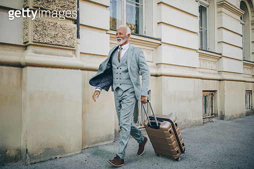 Businessman with a cool attitude walking through a city with a suitcase - gettyimageskorea