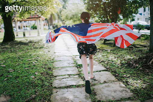 an asian chinese young girl wrapped in malaysia national flag running in public park - gettyimageskorea