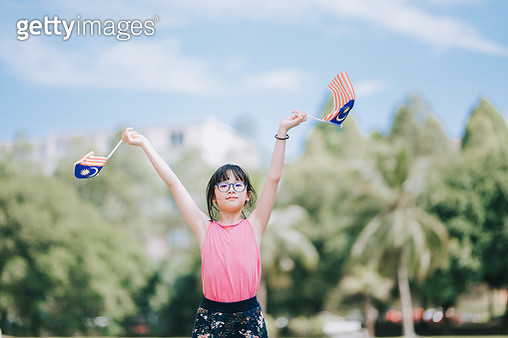 an asian chinese young girl waving malaysia national flag and looking at camera in public park - gettyimageskorea