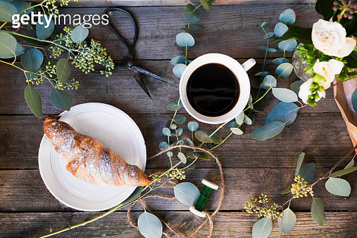 'Sweden, Coffee cup, croissant and flowers on wooden table' - gettyimageskorea