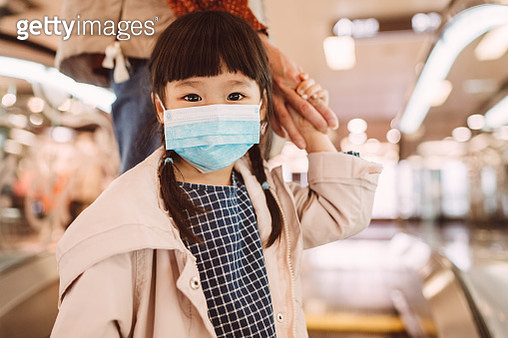 Little girl with medical face mask standing on escalator with mom - gettyimageskorea