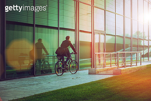 Rear view of a handsome man, on the way to work, riding bicycle beside the modern office building. The man is casually dressed and wears eyeglasses and carries black briefcase hung on shoulder. Blurred motion, copy space has been left. - gettyimageskorea