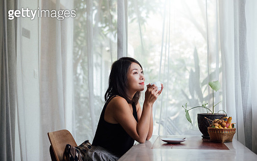 Young Woman Drinking Coffee Near Window At Home - gettyimageskorea