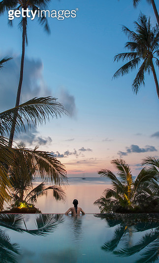 Young asian woman in an infinity pool among palms on the beach watching sunset on the Indian Ocean - gettyimageskorea