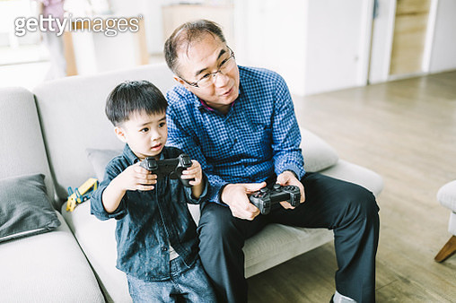 Grandfather and grandson playing video game at home. Elderly man is having fun with boy. They are sitting in living room. - gettyimageskorea