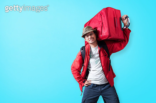 Portrait Of Mature Man Carrying Luggage Standing Against Blue Background - gettyimageskorea