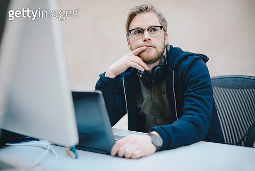 Thoughtful computer programmer sitting at desk in office - gettyimageskorea