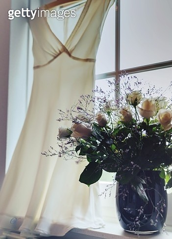 Flowers In Vase By Wedding Dress Hanging On Window - gettyimageskorea