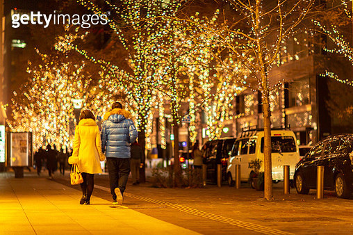 Rear View Of Couple Walking On Illuminated Sidewalk At Night - gettyimageskorea