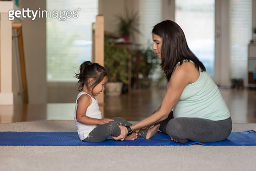 Pregant ethnic mother doing yoga with her young toddler girl - gettyimageskorea