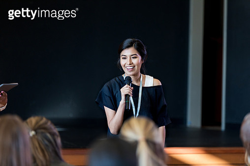 Young female influencer speaks with crowd during seminar - gettyimageskorea