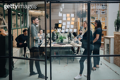 Business colleagues brainstorming in meeting at office seen through glass wall - gettyimageskorea