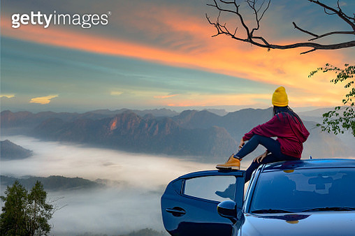 young woman sitting on the car roof with enjoy the nature of mist in the mountain at sunrise morning, - gettyimageskorea