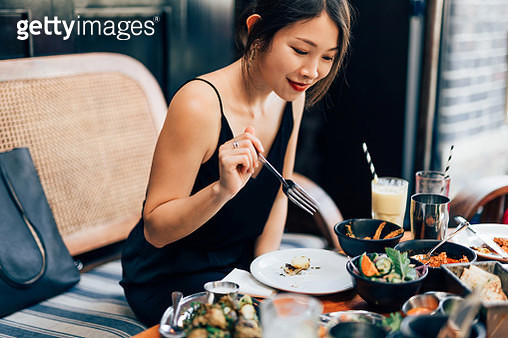 Young Woman Eating Food At The Restaurant - gettyimageskorea