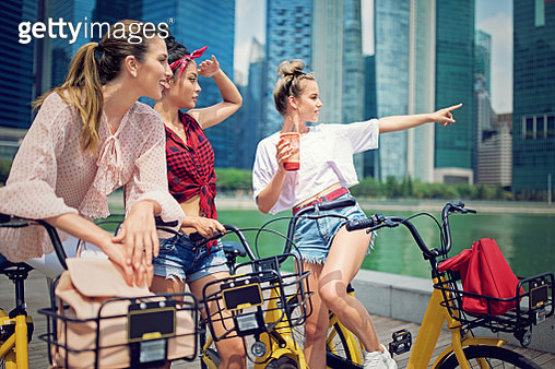 Girlfriends are talking and making fun at the front of the city skyscrapers - gettyimageskorea