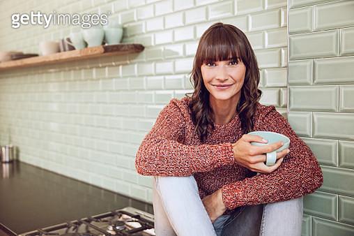 Happy woman sitting in kitchen, drinking tea - gettyimageskorea