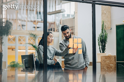 Businessman discussing with businesswoman sticking adhesive notes on glass wall in office - gettyimageskorea