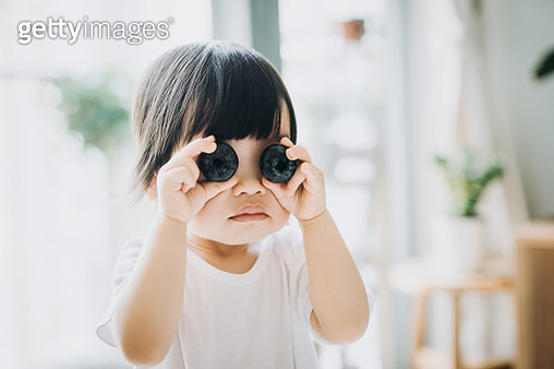 Playful little Asian toddler girl holding two huge blueberries over her eyes - gettyimageskorea