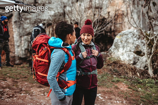 Two woman talking and preparing for hiking tour with group - gettyimageskorea