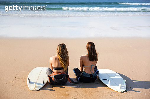 Rear View Of Female Friends Sitting At Beach - gettyimageskorea