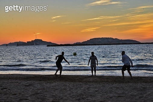 People Playing Soccer At Beach Against Sky During Sunset - gettyimageskorea