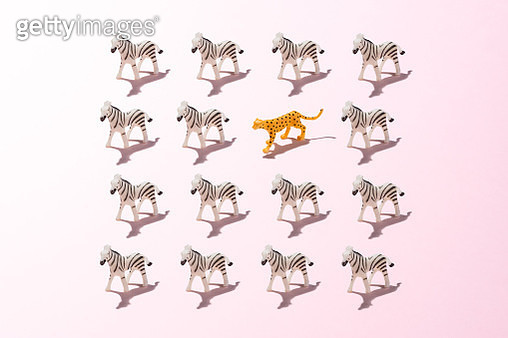 A Toy Leopard in a Crowd of Zebras on Pink Colored Background. - gettyimageskorea