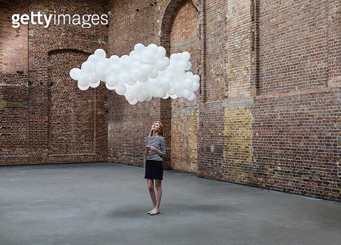 Young woman texting on mobile in empty warehouse with cloud made of balloons above head - gettyimageskorea