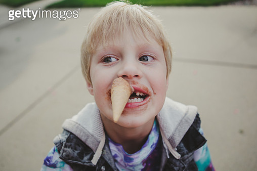 Boy with biting on an ice cream cone - gettyimageskorea