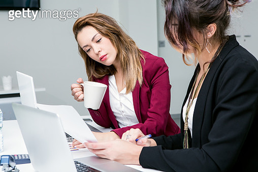 Businesswomen Using Laptop At Desk In Office - gettyimageskorea