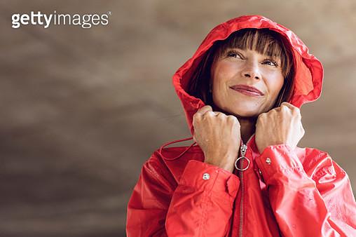 Woman wearing red rain coat, portrait - gettyimageskorea