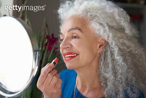 senior woman applying lipstick in mirror - gettyimageskorea