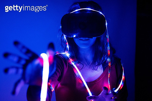 A woman wearing virtual reality glasses and rising the arm - gettyimageskorea